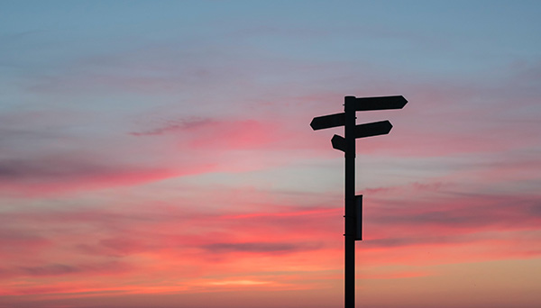 wooden sign post with the sunset on back